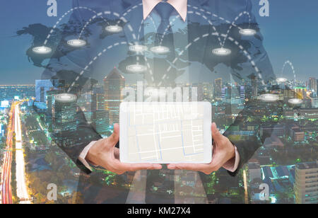 Businessman showing part of navigator map over the tablet screen on connection line over the world map with cityscape, - Stock Photo