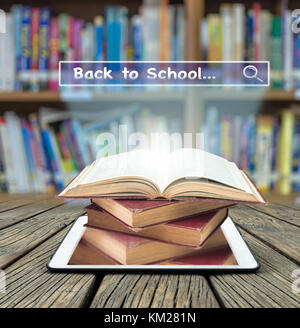 Tree growing from the old books over tablet on with browsing of Internet searching 'Back to school' bar on libraly - Stock Photo