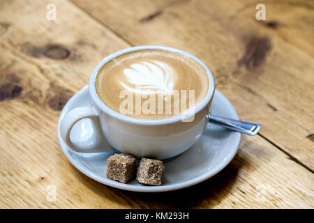 A freshly brewed latte coffee in a cup and saucer with two lumps of brown sugar. Placed on a table the milk artwork - Stock Photo