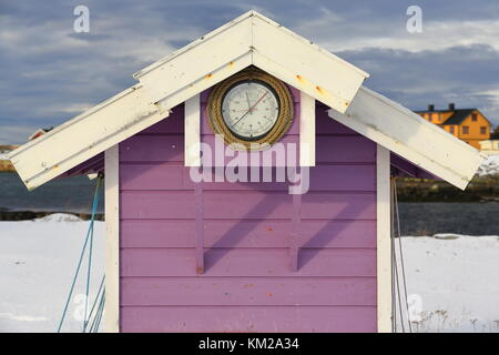 Mallow and white painted wooden-clapboard siding port booth with tidal clock on the wall under the white eaves roof - Stock Photo