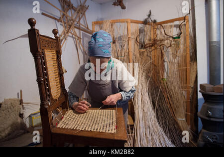 Mechernich, Germany. 02nd Dec, 2017. A basket maker working on the meshwork of an antique wooden chair in the LVR - Stock Photo