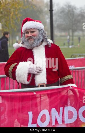 London, UK. 3rd Dec, 2017. Runners, joggers and walkers dressed in santa costumes brave the drizzly weather to participate - Stock Photo
