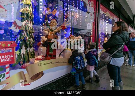Dublin, Ireland. 3rd Dec, 2017. Family admiring Christmas decoration in the windows of Arnotts store on Henry Street, - Stock Photo