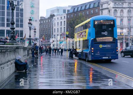 Dublin, Ireland. 3rd Dec, 2017. Homeless man begging on O`Connell bridge in Dublin on a rainy December day - Stock Photo