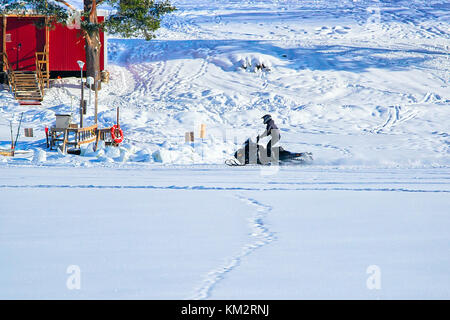 Man riding a snowmobile on the  iced lake at winter Rovaniemi, Lapland, Finland - Stock Photo