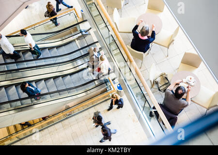 View from above of people in a shopping center taking the escalators, strolling along the walkways and having a - Stock Photo