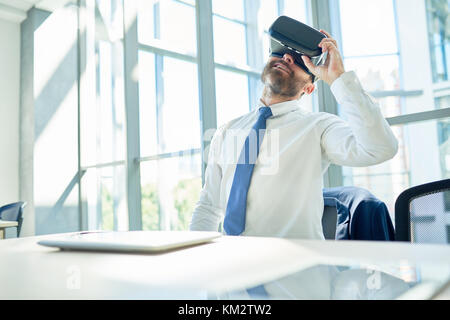 Mature Businessman Using VR Glasses in Office - Stock Photo