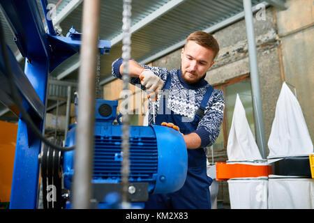 Man Repairing Machine Units at Factory - Stock Photo
