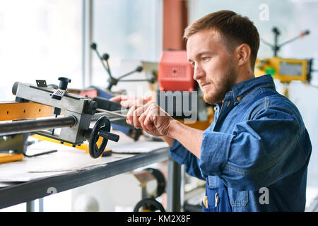 Young Man Using Machine Units at Factory - Stock Photo