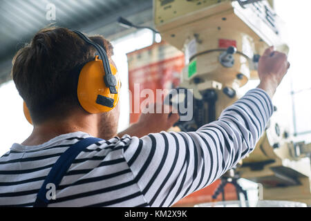 Back View of Worker Operating Machine Unit - Stock Photo