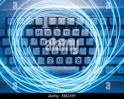 computer keyboard covered with snow illuminated by blue light with circles painted by blue light on a long exposure - Stock Photo