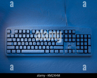 PC computer keyboard covered with snow illuminated by blue neon light with text merry christmas on buttons - Stock Photo