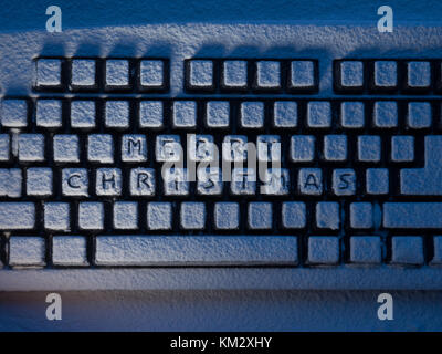 PC computer keyboard with text merry christmas on buttons covered with snow illuminated by light - Stock Photo