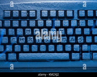 close up of computer keyboard with text merry christmas on buttons covered with snow illuminated by blue neon light - Stock Photo