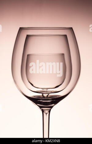 Three empty wineglass for red wine on diffusion lit background in abstract   composition with reflection, advertizing - Stock Photo