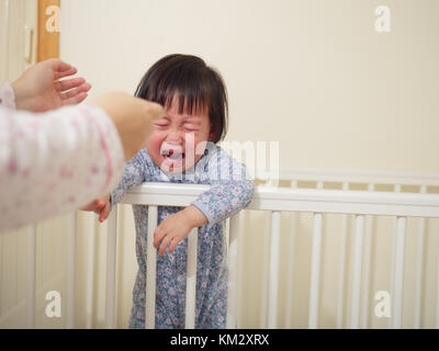 Crying Baby girl in cot bed - Stock Photo