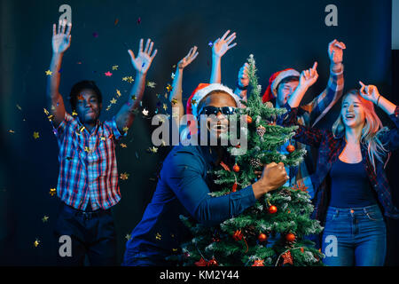 african american man hugging with cristmas tree - Stock Photo