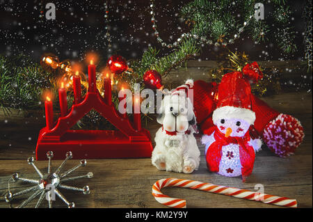 Snow man and Christmas symbols and New year on a wooden table with a Christmas lamp in rustic, cosy style. - Stock Photo