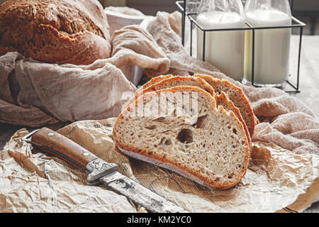 A beautiful loaf of sourdough bread from white wheat on a plate on a linen edge. Homemade pastries. - Stock Photo