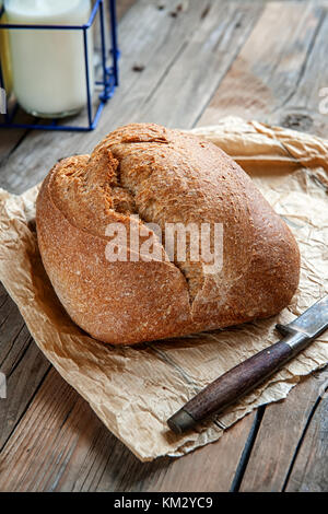 A beautiful loaf of sourdough bread from white wheat on a plate on a linen edge. Homemade pastries. In a rustic - Stock Photo