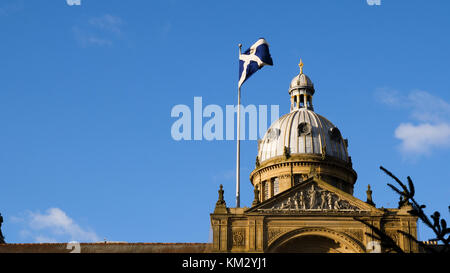 National flag of Scotland on a flagpole over Birmingham. - Stock Photo