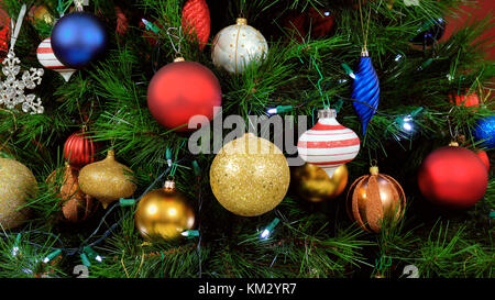 Festive Christmas Tree with brightl color decorations, close up focus on baubles - Stock Photo