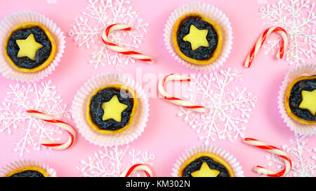 Festive collection of English style traditional Christmas holiday biscuits, cookies, and fruit mince pies, overhead on modern pink background.