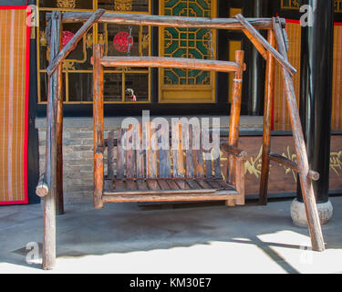 An antique twin seat swing made from chinese red pine. - Stock Photo