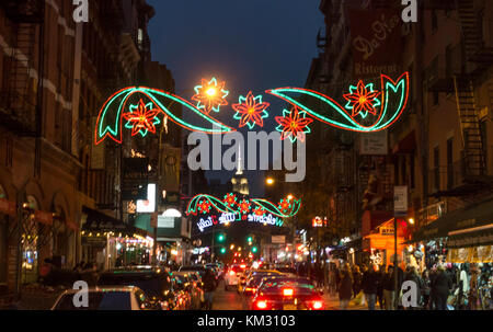 Colorful Christmas lighting on Mulberry Street  in Little Italy, New York City -- Empire State Building seen in - Stock Photo