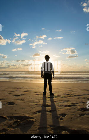 Silhouetted young boy standing on the beach at sunset - Stock Photo