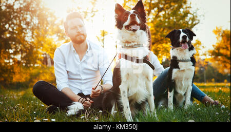 Romantic couple in love walking dogs in nature and smiling - Stock Photo