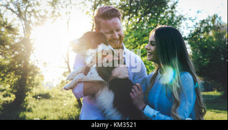 Romantic couple in love walking dogs and bonding - Stock Photo