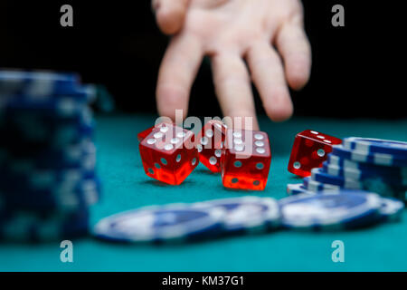 Picture of man throwing dice on table with chips in casino - Stock Photo