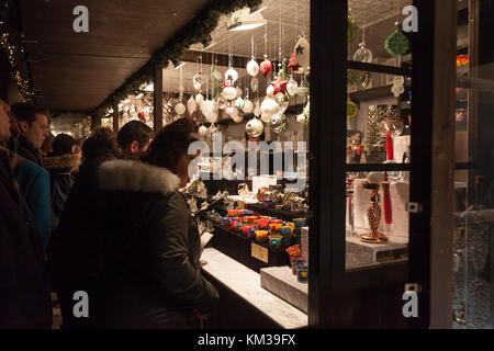 People browsing a stall sellikng gifts and decorations at Edinburgh's Christmas event 2017 in Princes Street Gardens. - Stock Photo