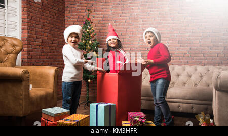 Indian Christmas - Indian girl child in santa clause attire coming out of gift box on christmas and 2 boys are surprised - Stock Photo