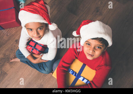 Indian kids celebrating christmas - cute little Indian kids playing, laughing and having fun with gift boxes on - Stock Photo