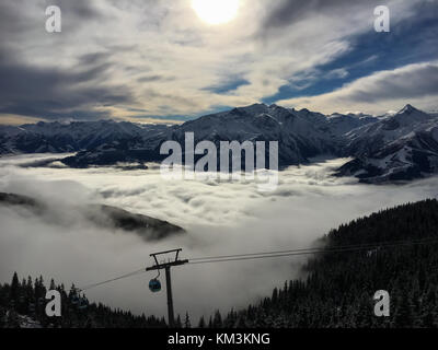 A blanket of clouds is lying over Lake Zell on a sunny winter day in the Austrian alps - Stock Photo