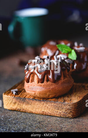 Mini chocolate bundt cake with chocolate ganache and mint leaf on wooden cutting board. Closeup view, selective - Stock Photo