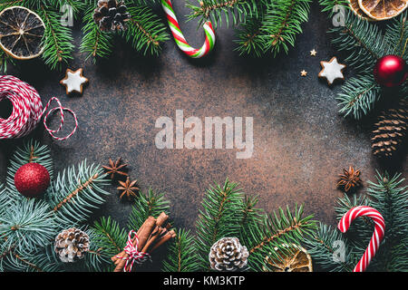 Christmas frame with fir tree branches, candy canes, gingerbread cookies, spices and dried oranges. Copy space for - Stock Photo