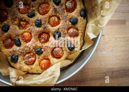 Close up of a typical Apulian focaccia in a tin tray on a wooden board. Flat lay. Landscape format. - Stock Photo
