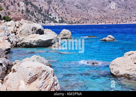 turquoise water with rocks on Apella beach - Stock Photo