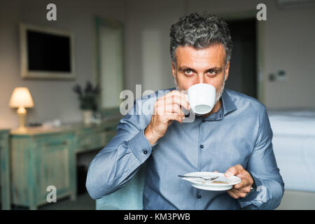 Mature businessman drinking coffee in a hotel room. - Stock Photo