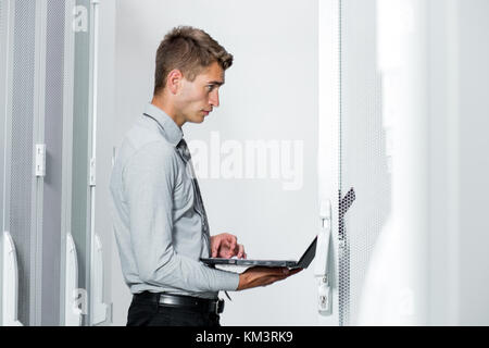Portrait of modern young man holding laptop standing in server room working with supercomputer - Stock Photo