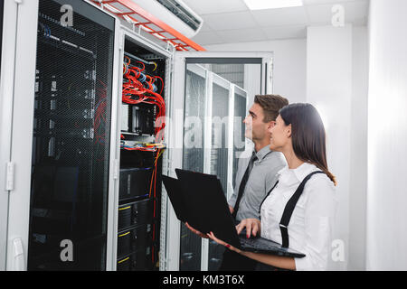 team of busienss people working in server room - Stock Photo