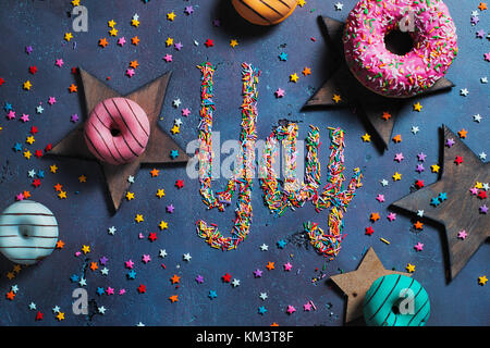Exclamation Yay written with sprinkles on a stone background with donuts and stars. Party preparation concept. - Stock Photo