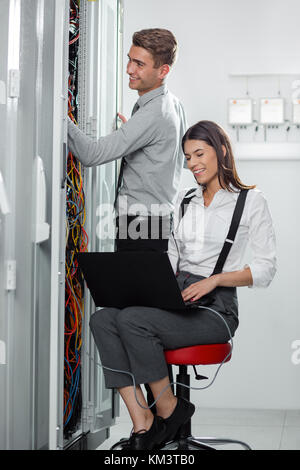 Team of technicians working together on servers at the data centre - Stock Photo