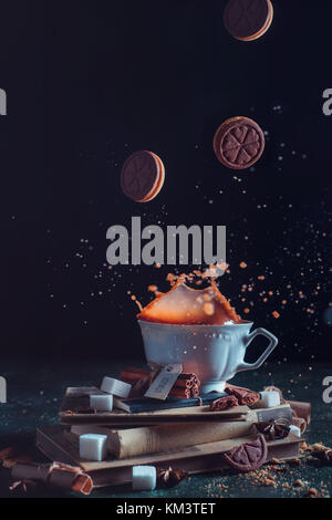 Porcelain tea cup with falling cookies and a splash on a dark background. Frozen motion food photography. - Stock Photo