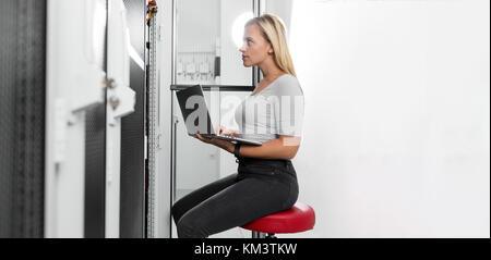 Portrait of technician working on laptop in server room - Stock Photo