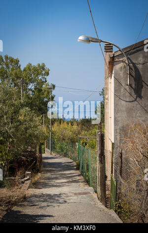 A street of Acquafredda di Maratea, a little village in Basilicata, Italy. Blue sea in the background. - Stock Photo
