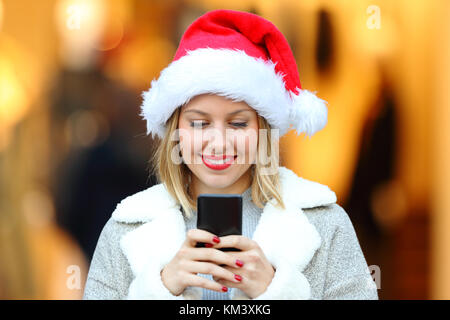 Front view portrait of a happy girl sending smart phone messages in christmas holidays on the street - Stock Photo